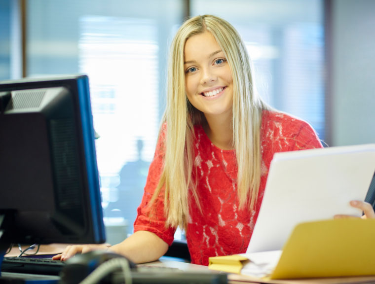 Smiling intern sitting at computer holding papers