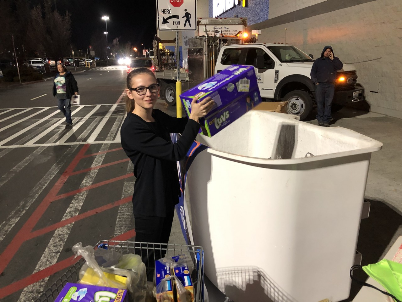 Woman putting boxes into a line truck bucket outside of Walmart.
