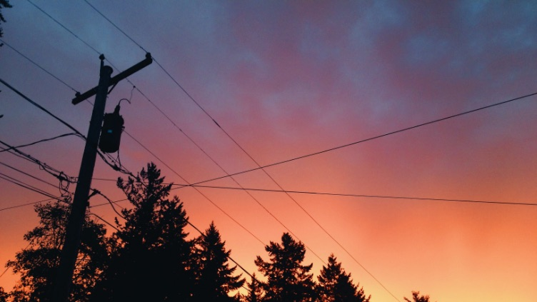 overhead power lines with sunset in background