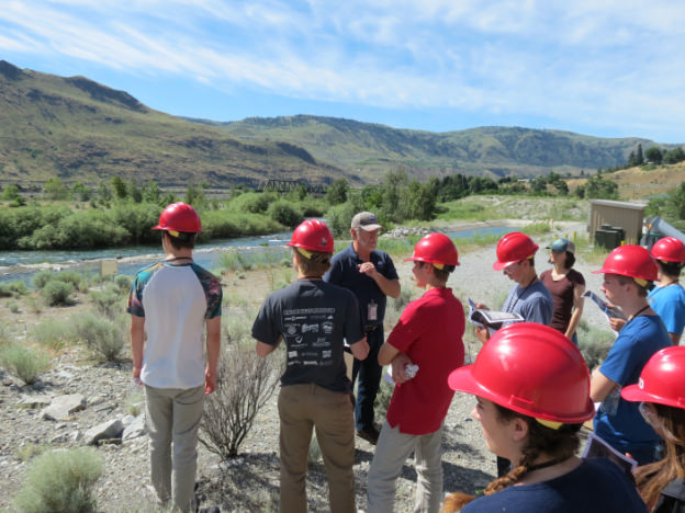 Students in hard-hats listen to tour guide near river