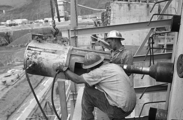 Black and white historical image of two dam workers