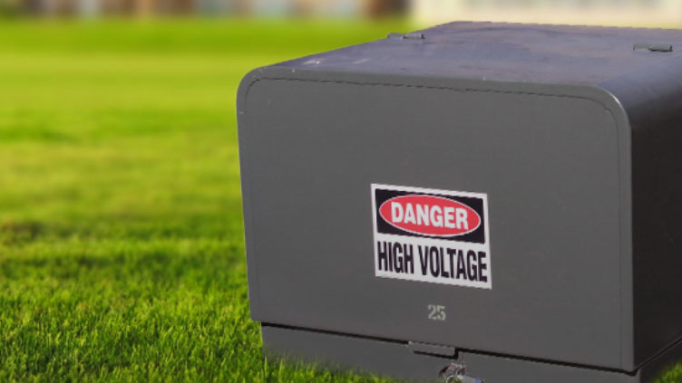 dark green electrical box with sticker that says danger, high voltage.